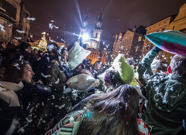 Young people enjoy a pillow fight at the Old Town Square in Prague, Czech Republic, 22 December 2016. (Photo by Filip Singer/EPA)