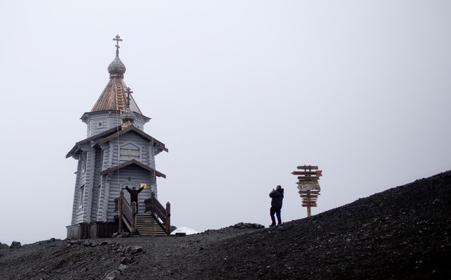 In this January 28, 2015 photo, tourists take pictures at the entrance of the world's southernmost Eastern Orthodox church, the Holy Trinity, located on top of a rocky hill on King George Island, Antarctica. Russian priests here rotate in for yearlong stints, primarily to celebrate Mass for the workers on the Russian Bellinghausen base. (Photo by Natacha Pisarenko/AP Photo)