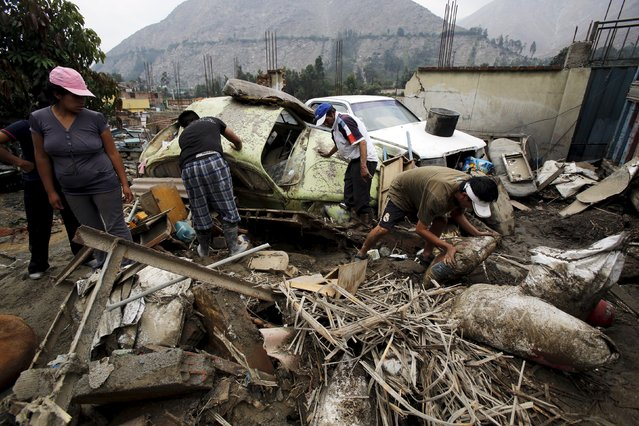 People remove debris of cars and houses after a massive landslide in Chosica, March 24, 2015. (Photo by Mariana Bazo/Reuters)