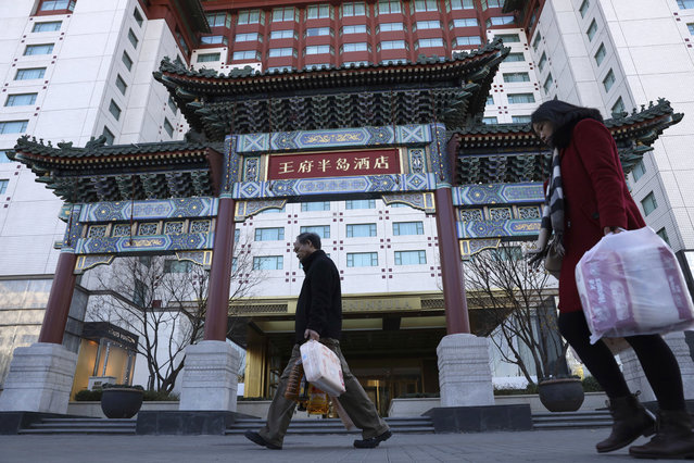 Residents passes by The Peninsula hotel which announced that it was investigating claims in an online video that supposedly showed the hotel cleaners using dirty towels to wipe cups and sinks in Beijing Friday, November 16, 2018. The Chinese tourism ministry asked authorities in Beijing, Shanghai and three provinces to investigate room cleaning at 14 major hotels after hidden camera video showed workers using used towels to clean cups and glasses and other questionable practices. (Photo by Ng Han Guan/AP Photo)