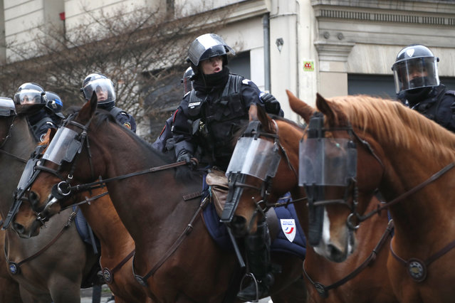 Mounted Police officers on their horses take their positions during clashes with yellow-vested protesters, in Paris, France, Saturday, December 8, 2018. (Photo by Thibault Camus/AP Photo)