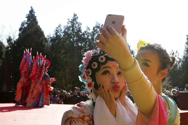 Chinese dancers dressed in traditional costume take a selfie in backstage during a temple fair for a Lunar New Year celebration in Beijing, Monday, February 8, 2016. (Photo by Andy Wong/AP Photo)