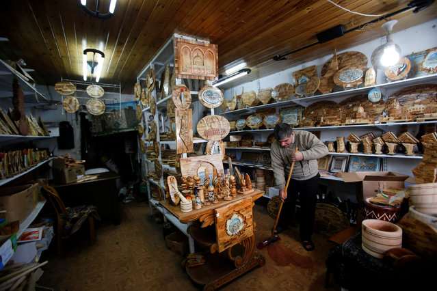 Palestinian Yahiya Idress, who makes decorative objects from olive wood to be sold as souvenirs, cleans his shop in the West Bank city of Hebron November 22, 2016. (Photo by Mussa Qawasma/Reuters)