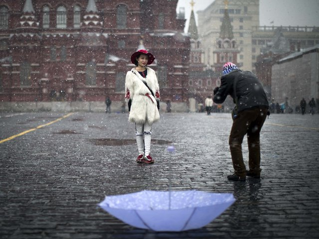 Chinese tourists take photographs at Red Square during a snowfall in Moscow, Russia, Friday, April 3, 2015. (Photo by Alexander Zemlianichenko/AP Photo)
