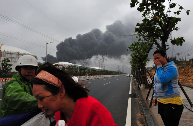In this photo released by Xhinhua News Agency, a rescuer evacuates residents near the site of a chemical plant blast in Zhangzhou, southeast China's Fujian Province Tuesday, April 7, 2015. Six people have been hospitalized and hundreds of firefighters deployed to battle a blaze sparked by an explosion at Goure PX Plant that produces the toxic chemical paraxylene, officials said Tuesday. (Photo by Wei Peiquan/AP Photo/Xinhua)