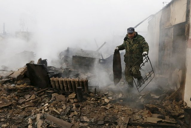 Local resident Sergei Shvedchikov, 61, carries scrap metal from his burnt house in the settlement of Shyra, damaged by recent wildfires, in Khakassia region, April 13, 2015. (Photo by Ilya Naymushin/Reuters)