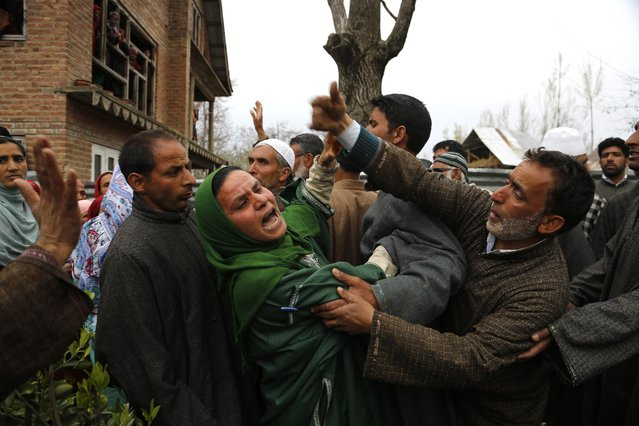 An unidentified relative of Mushraq Ahmad, an Indian policeman shot dead by suspected rebels, wails during his funeral procession in Arigam, some 32 Kilometers (20 miles) south of Srinagar, Indian controlled Kashmir, Monday, April 6, 2015. Suspected rebels fatally shot three unarmed policemen Monday in the disputed Himalayan region of Kashmir, officials said. (Photo by Mukhtar Khan/AP Photo)