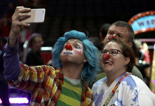 """A Ringling Bros. and Barnum & Bailey clown takes a selfie with Jennifer and Kevin Fox, of Fort Pierce, Fla., during a pre show for fans Saturday, January 14, 2017, in Orlando, Fla. The Ringling Bros. and Barnum & Bailey Circus will end the """"The Greatest Show on Earth"""" in May, following a 146-year run of performances. Kenneth Feld, the chairman and CEO of Feld Entertainment, which owns the circus, told The Associated Press, declining attendance combined with high operating costs are among the reasons for closing. (Photo by Chris O'Meara/AP Photo)"""