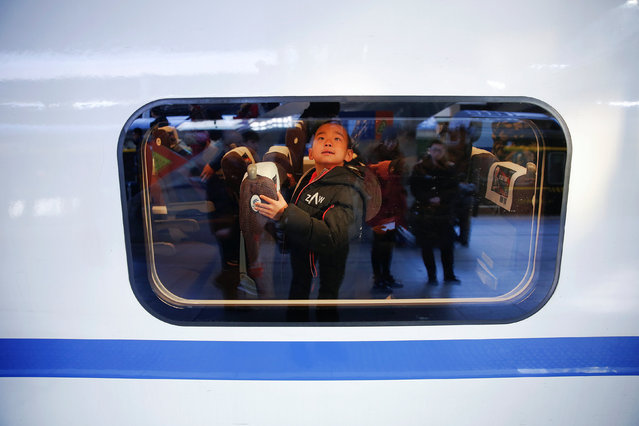 A boy checks his seat on a passenger train he boarded at the Beijing Railway Station in central Beijing, China January 13, 2017 as the annual Spring Festival travel rush begins ahead of the Chinese Lunar New Year. (Photo by Damir Sagolj/Reuters)