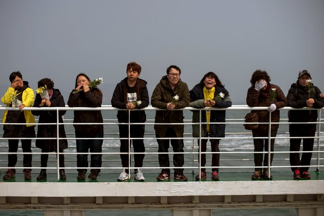 Relatives of victims of the Sewol ferry disaster weep as they stand on the deck of a boat during a visit to the site of the sunken ferry, off the coast of South Korea's southern island of Jindo April 15, 2015. (Photo by Ed Jones/Reuters)