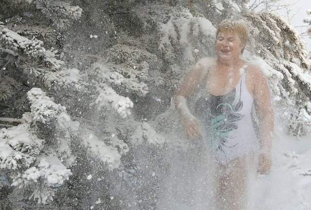 Lyubov Valiyeva, a member of the Cryophile amateur winter swimming club, sprinkles herself with snow from branches of a pine, part of her daily winter training session, on the bank of the Yenisei River, with the air temperature at about minus 33 degrees Celsius (minus 27.4 degrees Fahrenheit), in Krasnoyarsk, Russia, January 17, 2017. (Photo by Ilya Naymushin/Reuters)