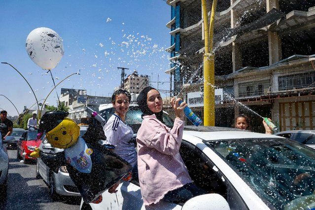 """Palestinian high school students spray foam from a car window as they celebrate on the street after passing their final exams known as """"Tawjihi"""", in the West Bank city of of Hebron, on August 3, 2021. (Photo by Hazem Bader/AFP Photo)"""