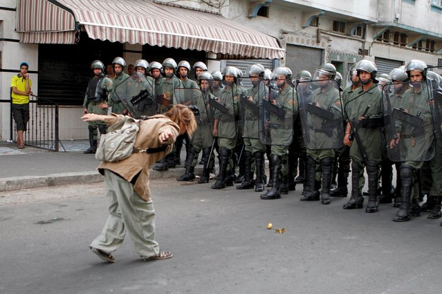 """A pro-democracy demonstrator gestures at policemen during a protest organised by the """"February 20 Movement"""", who are demanding political reforms, in Casablanca, in this May 29, 2011 file photo. (Photo by Reuters/Macao)"""