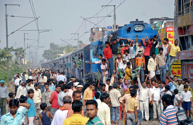 Supporters of India's Rashtriya Janata Dal party block the path of a passenger train during a protest against rising inflation on the outskirts of the eastern Indian city of Patna, April 27, 2010. (Photo by Krishna Murari Kishan/Reuters)