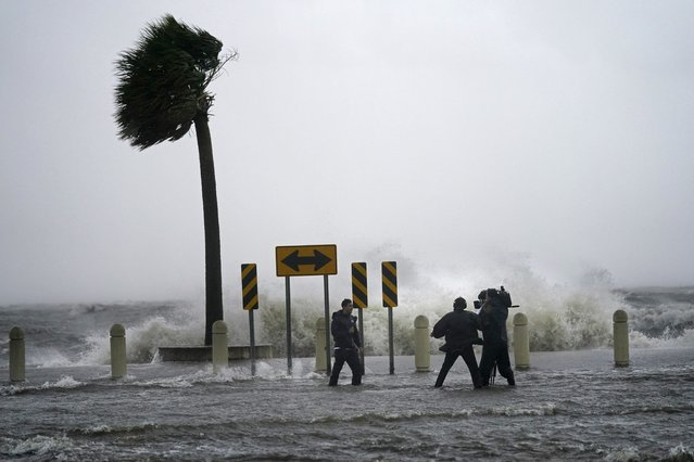 A news crew reports on the edge of Lake Pontchartrain ahead of approaching Hurricane Ida in New Orleans, Sunday, August 29, 2021. (Photo by Gerald Herbert/AP Photo)