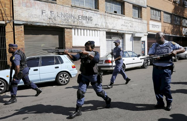 Police officers fire rubber bullets as they disperse African immigrants who are carrying machetes in Johannesburg, April 17, 2015. (Photo by Siphiwe Sibeko/Reuters)