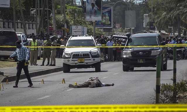 In this image made from video, security forces, forensic experts and onlookers gather near a body in the street near the French embassy in Dar es Salaam, Tanzania Wednesday, August 25, 2021. Tanzania's president said five people are dead, including three police officers, after a gun battle with an armed man near the French Embassy in Dar es Salaam. (Photo by AP Photo/Stringer)