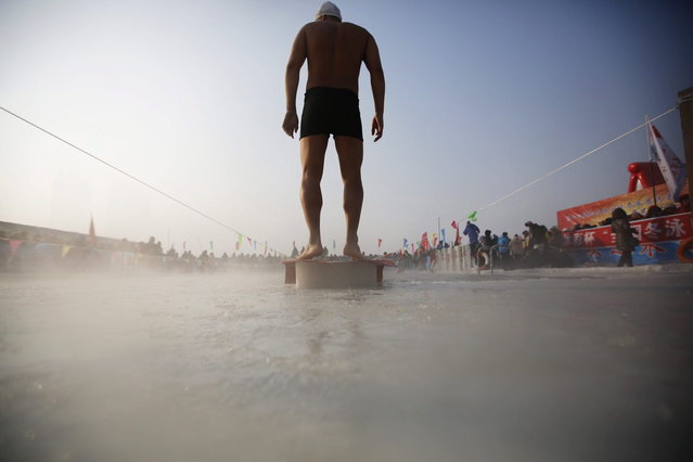 A swimmer stands on a platform on a pool carved into the thick ice covering the Songhua River during the Harbin Ice Swimming Competition in the northern city of Harbin, Heilongjiang province January 5, 2014. (Photo by Kim Kyung-Hoon/Reuters)