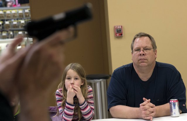Joanna Zuber and her father Ken Zuber listen to instructor Jerry Kau during a Youth Handgun Safety Class at GAT Guns in East Dundee, Illinois, April 21, 2015. (Photo by Jim Young/Reuters)