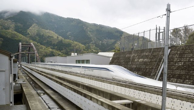 A magnetically levitating train operated by Central Japan Railway Co. making a test run is seen on an experimental track in Tsuru, Yamanashi Prefecture, in this photo taken by Kyodo April 21, 2015. Japan's experimental magnetically levitating train or maglev managed to break the new world speed record on Tuesday with a top speed of 603 kilometres (374 miles) per hour, Central Japan Railway, also known as JR Tokai said. (Photo by Reuters/Kyodo News)