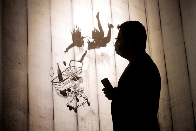 """A guest attends the preview of the Banksy: """"Genius or Vandal?"""" exhibit in New York City, U.S., September 1, 2021. (Photo by Brendan McDermid/Reuters)"""