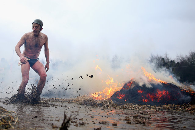 A competitor runs past a fire during the Tough Guy Challenge on January 26, 2014 in Telford, England.  (Photo by Bryn Lennon/Getty Images)