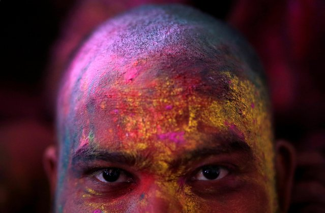 "A man daubed in colours looks on as he takes part in ""Lathmar Holi"" celebrations inside a temple in the town of Barsana, in Uttar Pradesh, India, March 15, 2019. (Photo by Altaf Hussain/Reuters)"