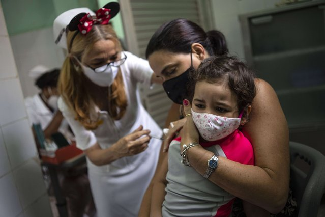A mother holds her daughter who is injected with a dose of the Soberana-02 COVID-19 vaccine, in Havana, Cuba, Thursday, September 16, 2021. Cuba began inoculating children as young as 2-years-old with locally developed vaccines on Thursday. (Photo by Ramon Espinosa/AP Photo)