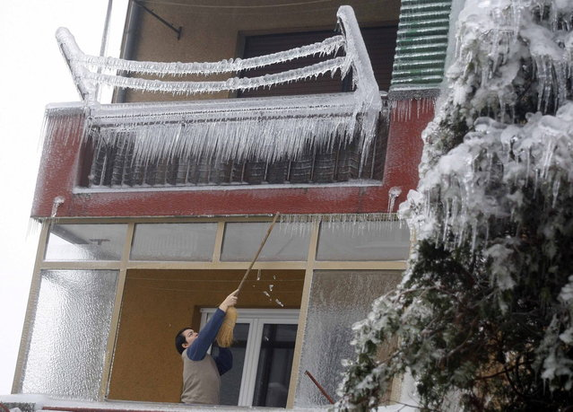 A woman clears off icicles with a broom from a balcony in Postojna February 5, 2014. (Photo by Srdjan Zivulovic/Reuters)