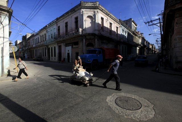 Cubans pushing a cart with bags of cement on a street in Havana March 8, 2016. (Photo by Enrique de la Osa/Reuters)