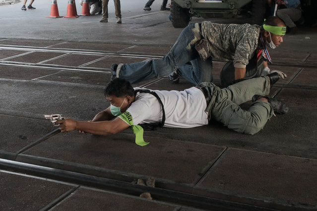 A Thai anti-government protester takes cover and aims his gun before shooting towards Thai pro-election protesters (not seen) in Bangkok on February 1, 2014. Violence erupted in Bangkok on February 1, the eve of tense Thai elections, with explosions and heavy gunfire breaking out in clashes between pro- and anti-government protesters, according to an AFP journalist. (Photo by Nicolas Asfouri/AFP Photo)