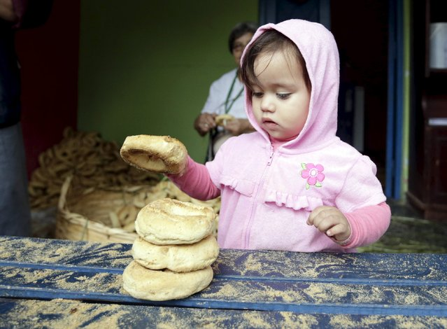 "Ximena Antar holds a traditional cheese and corn bun called a ""chipa"", as her family decorates an altar in celebration of Kurusu Ara in Asuncion May 3, 2015. (Photo by Jorge Adorno/Reuters)"