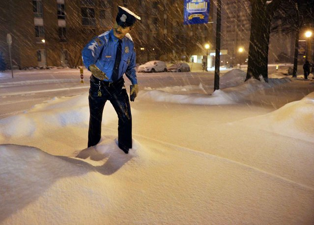 A view of a statue of a police man ankle deep in snow in Chevy Chase, Maryland, in the early hours of February 13, 2014. A deadly ice storm stranded scores of people on slick roads and knocked out power to hundreds of thousands of US homes as winter-weary Americans dug in against Mother Nature's latest blow. Accumulation of between 4 to 8 inches, 10 to 20 cm, was expected by the morning. (Photo by Mandel Ngan/AFP Photo)