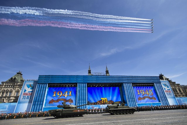 Russian military planes fly over, as  Russian T-14 Armata tank is ready to be towed at the Red Square during a preparation for general rehearsal for the Victory Day military parade which will take place at Moscow's Red Square on May 9 to celebrate 70 years after the victory in WWII, in Moscow, Russia, Thursday, May 7, 2015. (Photo by Alexander Zemlianichenko/AP Photo)