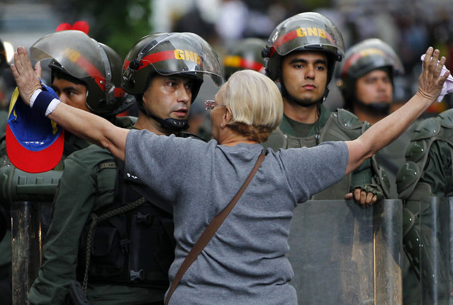 An opposition supporter shouts at a riot police officer during a protest against President Nicolas Maduro's government in Caracas February 17, 2014. Venezuela ordered the expulsion of three U.S. diplomats on Monday on charges of recruiting university students to lead demonstrations that have left three dead in the OPEC nation's most serious violence since President Nicolas Maduro's election in April. (Photo by Carlos Garcia/Reuters)