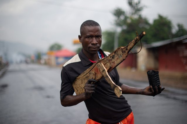 A man poses with a wooden rifle in the Musaga neighbourhood in Bujumbura, Burundi on May 5, 2015. Burundi, where a 13-year civil war between Tutsis and Hutus ended only in 2006, has been rocked by violent protests since the ruling party designated President Pierre Nkurunziza to run in elections for a third term, in apparent defiance of the constitution and the Arusha accords which ended the war. (Photo by Phil Moore/AFP Photo)
