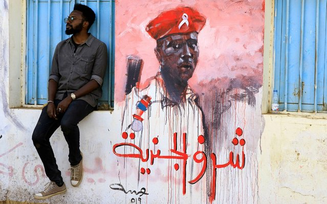 A Sudanese youth takes rest near a revolutionary mural reading in arabic 'the honor of a soldier', in a street of Khartoum, Sudan, 23 April 2019. Sudanese protesters continue their sit in and gatherings near the army head quarters in a bid to pressure for a civilian council instead of the current military one, after the resignation of President Omar al-Bashir on 11 April. Some 50 protesters were killed since December 2018 when the protesters asking for a change of regime started. (Photo by EPA/EFE/Rex Features/Shutterstock/Stringer)