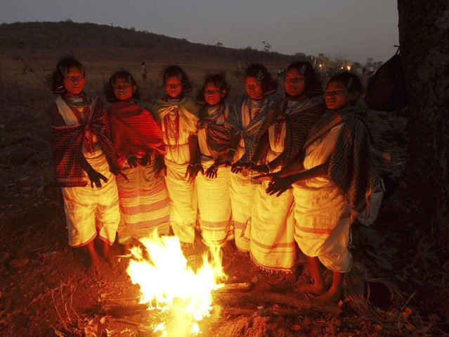 Female members of Dongria tribe warm themselves near a fire during the two-day long Niyamraja Festival atop the Niyamgiri hills near Lanjigarh in Kalahandi district, Orissa state. (Photo by Biswaranjan Rout/AP Photo)