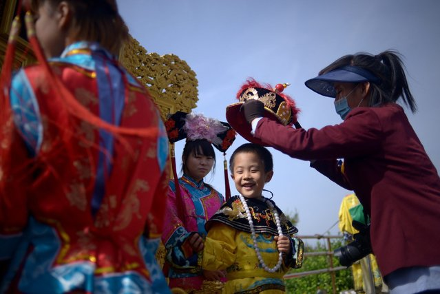 """A boy prepares to wear the costume of a Qing dynasty emperor for a portrait session at a park near the Forbidden City in Beijing on May 3, 2015. China will create a """"blacklist"""" of its tourists who behave badly overseas, state-media reported, after several embarrassing incidents involving Chinese travelling abroad. (Photo by Wang Zhao/AFP Photo)"""