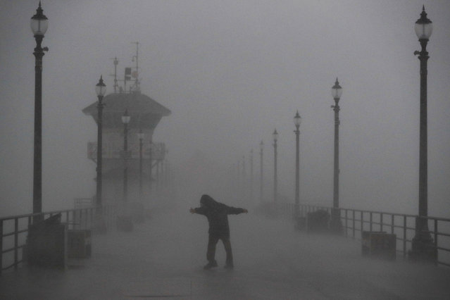 A man struggles against gusty wind and heavy rain as he walks along a pier Friday, February 17, 2017, in Huntington Beach, Calif. A major Pacific storm has unleashed downpours and fierce gusts on Southern California, triggering flash flood warnings and other problems. (Photo by Jae C. Hong/AP Photo)