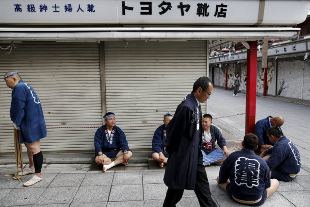 Revellers wear traditional short coats as they wait for the arrival of a portable shrine during the Sanja Matsuri festival in the Asakusa district of Tokyo May 17, 2015. (Photo by Thomas Peter/Reuters)