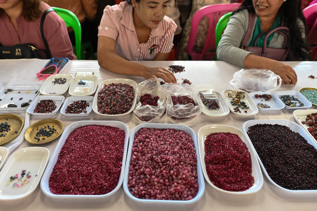 This photo taken on May 17, 2019 shows sellers trading rubies and other gemstones at the gems market in Mogok town, north of Mandalay. (Photo by Ye Aung Thu/AFP Photo)