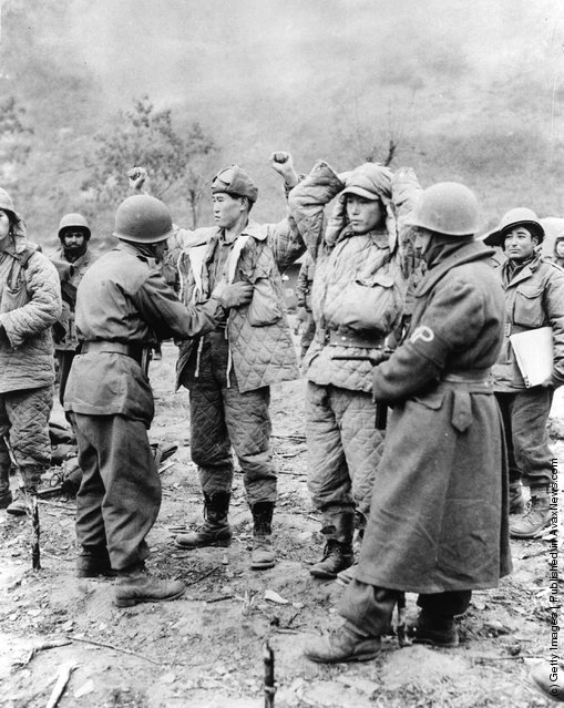 Turkish UN troops search captured Chinese troops for weapons during the Korean War