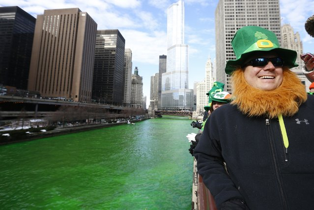 A man dressed as a leprechaun smiles as he stands beside the dyed green Chicago River during St. Patrick's Day celebrations in Chicago March 15, 2014. (Photo by Jim Young/Reuters)