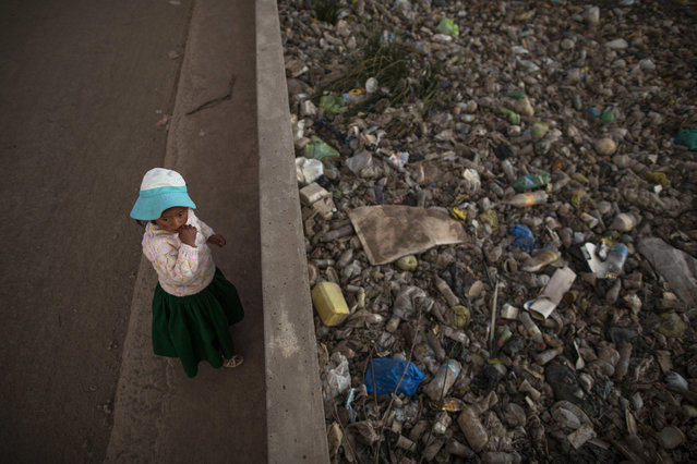 In this February 1, 2017 photo, Maria Jose Campos Inquilla stands next to the trash-filled Torococha River near a municipal waste treatment plant that feeds into Lake Titicaca, in Juliaca, in the Puno region of Peru. In 2011, then-presidential candidate Ollanta Humala promised to resolve the contamination and construct water sewage processing plants. He won 79 percent of votes in the Lake Titicaca region but did not follow through. (Photo by Rodrigo Abd/AP Photo)