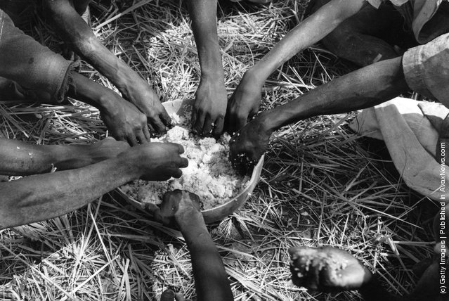 1950: Rice field workers taking their lunch from a communal bowl