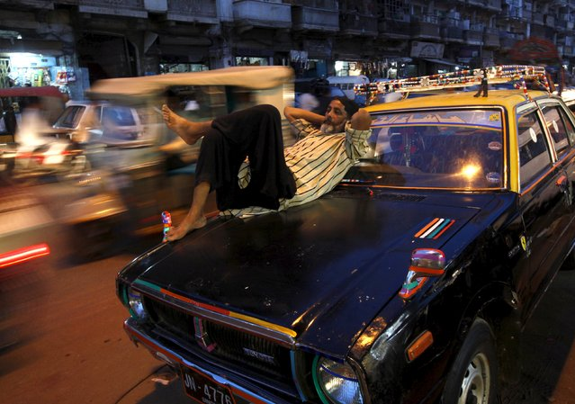 Vehicles move past a man resting on a taxi, as he waits for passengers, along a road in Karachi, Pakistan, May 5, 2015. (Photo by Akhtar Soomro/Reuters)