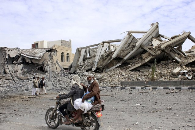 People ride on a motorcycle as they pass by a police headquarters destroyed by a Saudi-led air strike in Yemen's northwestern city of Saada May 7, 2015. (Photo by Reuters/Stringer)