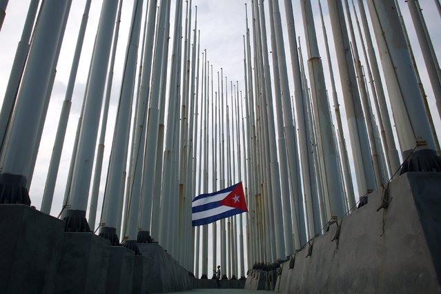 A man lowers the Cuban flag while standing amidst flag posts installed outside the U.S. embassy in Havana, April 16, 2016. (Photo by Alexandre Meneghini/Reuters)