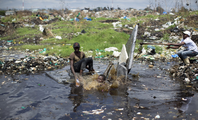 In this photo taken Thursday, November 12, 2015, a boy who scavenges for a living dives off the makeshift raft he and his friends have made for fun, into a dark and polluted pool of water left by recent rains, at the garbage dump in the Dandora slum of Nairobi, Kenya. Men, women and children traipse through the murky sludge that weaves through mountains of garbage in Nairobi's notorious Dandora dump, hunting for anything that can be recycled to earn themselves enough for their daily bread – some of the poorest of Kenya's poor and those likely to be on Pope Francis' mind when he makes his first trip to Africa this week and brings his message of environmental stewardship and care for society's most marginal. (Photo by Ben Curtis/AP Photo)
